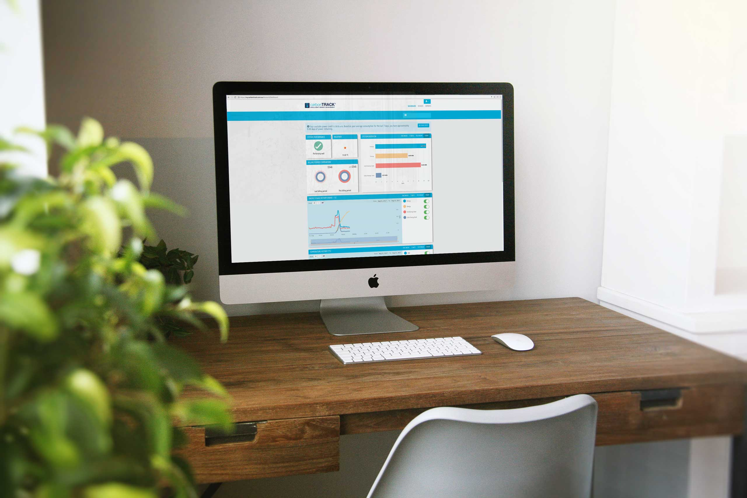 A computer, sitting atop a wooden desk in a home, shows the carbonTRACK online dashboard