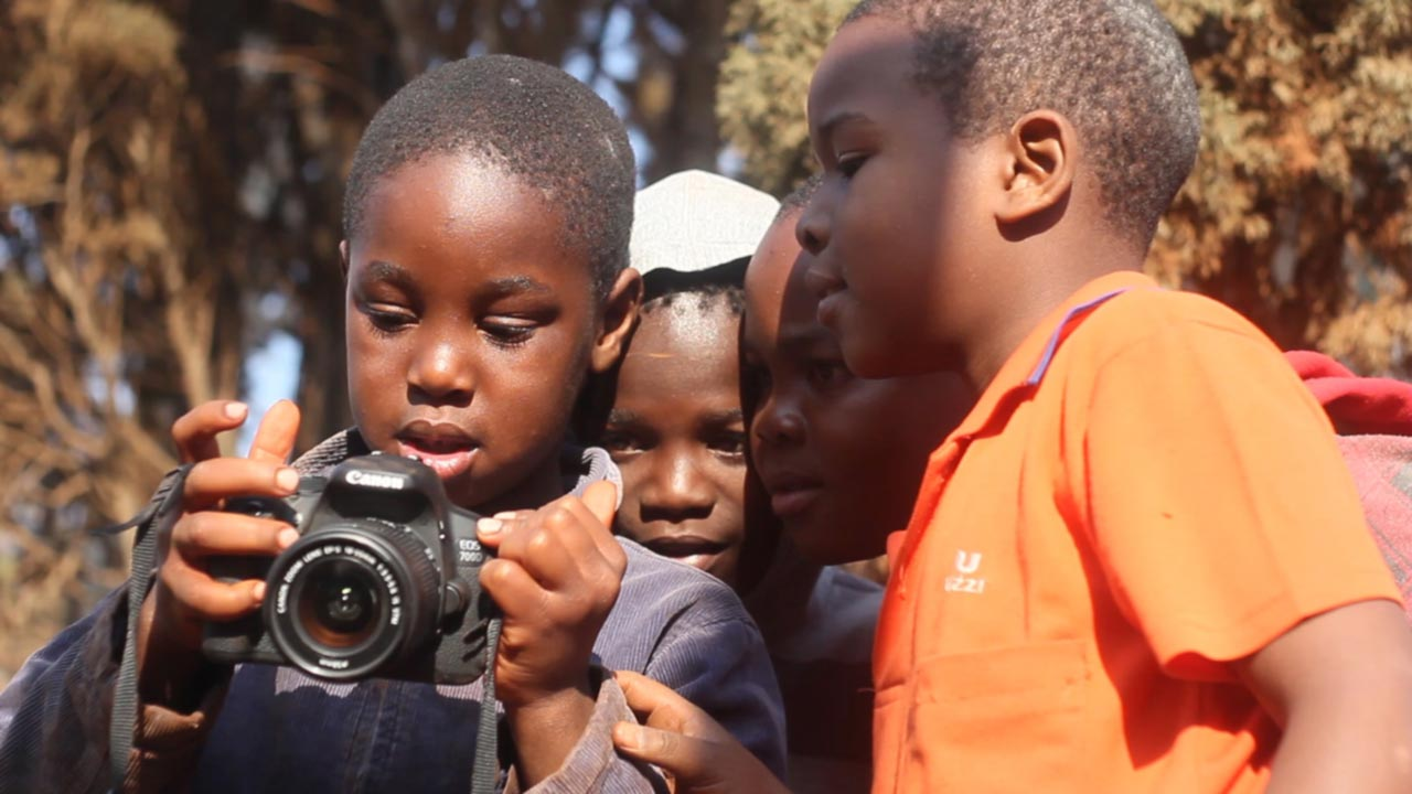 Four young African boys curiously look at the screen of a DSLR camera.
